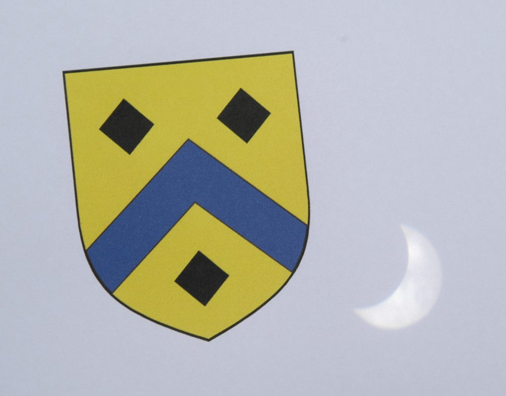 [2017 solar eclipse projected beside the River Houses coat of arms]